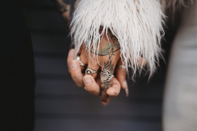 hipster bohemian couple hold tattooed hands by New Orleans Elopement Photographer as they prepare to walk into the French quarter.