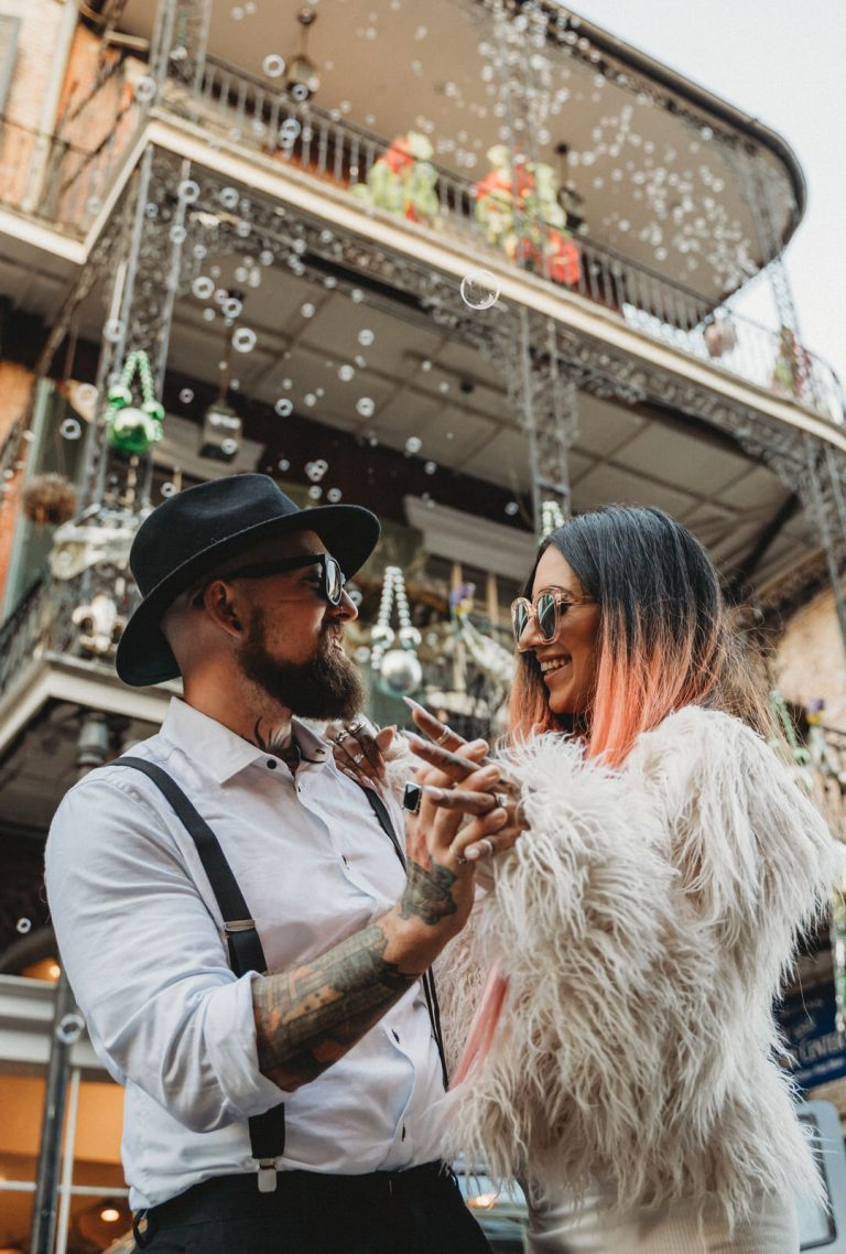 hipster couple eloping as photographed by New Orleans Elopement Photographer near bourbon street. She wears a fur coat as he sports his overalls, dancing as bubbles fall on them in the French Quarter.