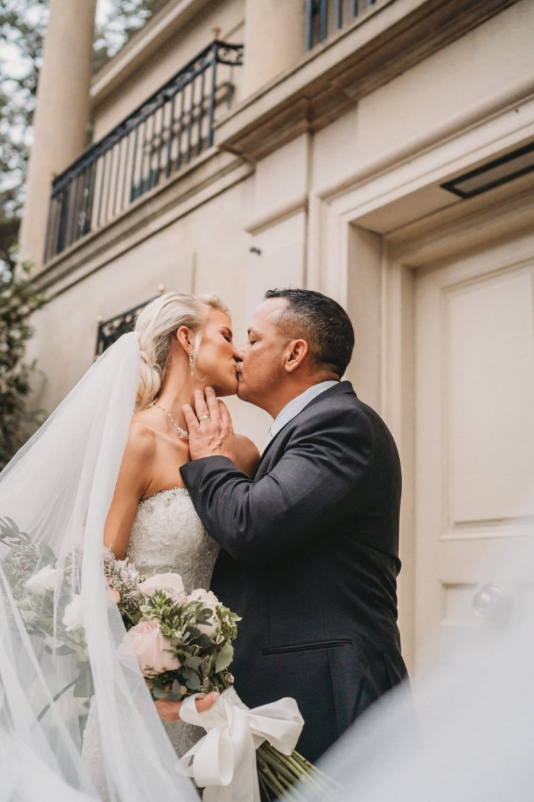 married couple veil kiss during shoot at Longue Vue House and Gardens for New Orleans Elopement Photographer