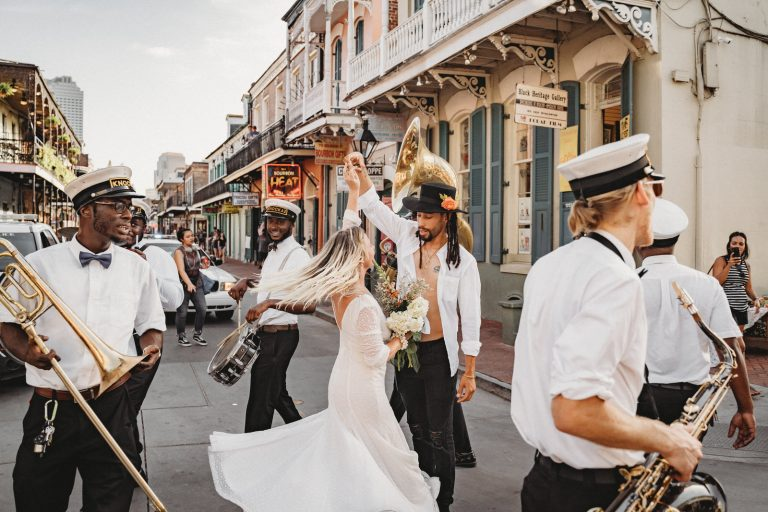 eloping couple second line down bourbon with New Orleans Elopement Photographer